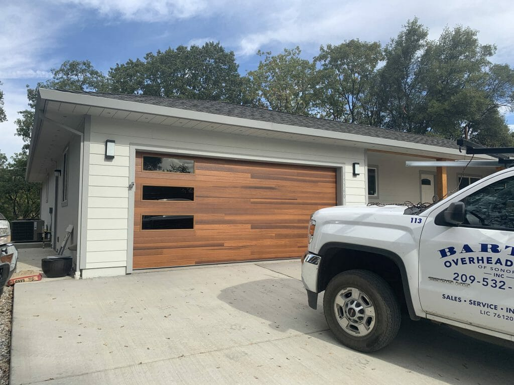 The picture shows a cedar plank style garage door installed with a truck in front.