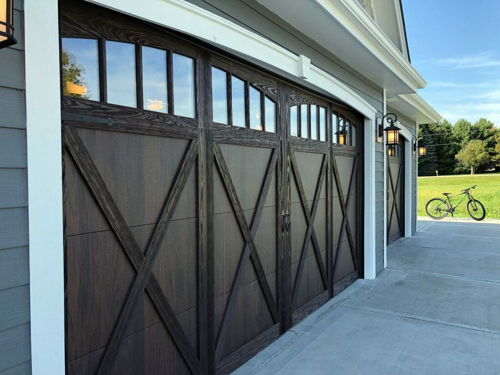 Wood overlay garage doors installed in a garage.