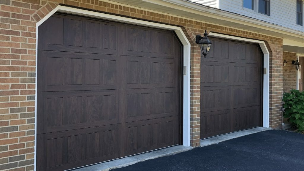 Two CHI Shaker Panel garage doors installed in a brick garage.