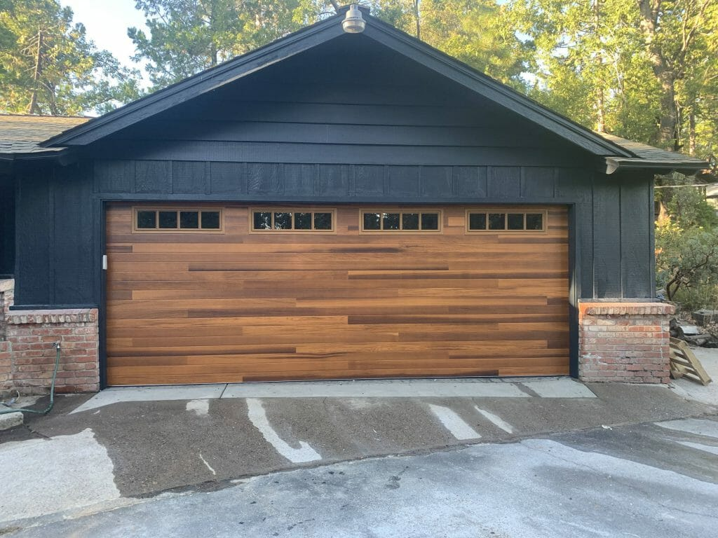 The picture shows a garage with a new wood garage door installed.