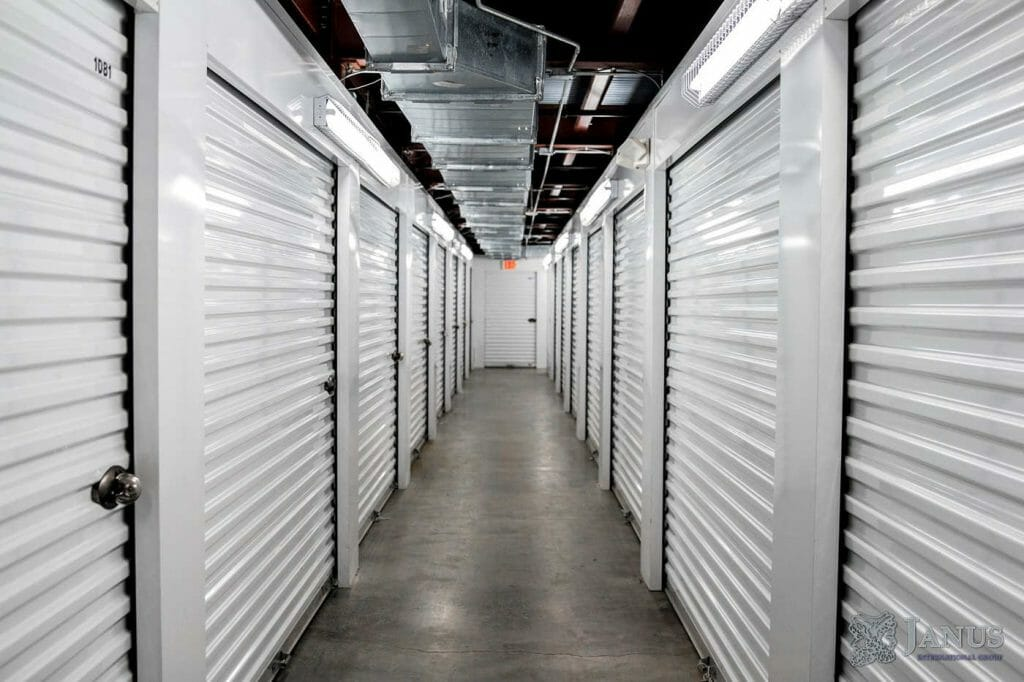 A hallway of white storage closets, each with a door.