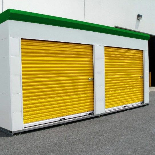 Two yellow self storage doors on a small shed.