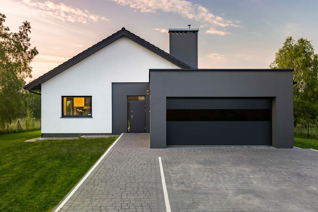 black and white home with a glass garage door.