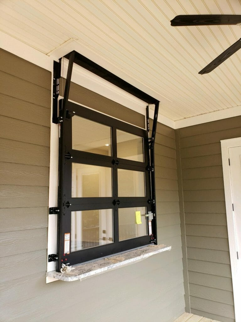 A small glass garage door installed in a window.